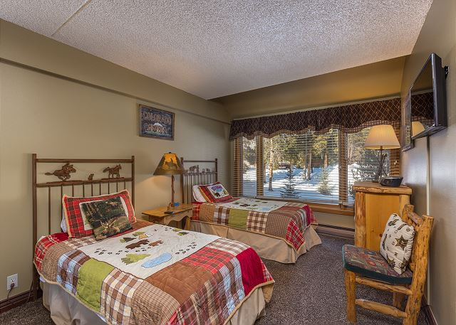 The third guest bedroom has two twin-sized beds and a flat screen TV.