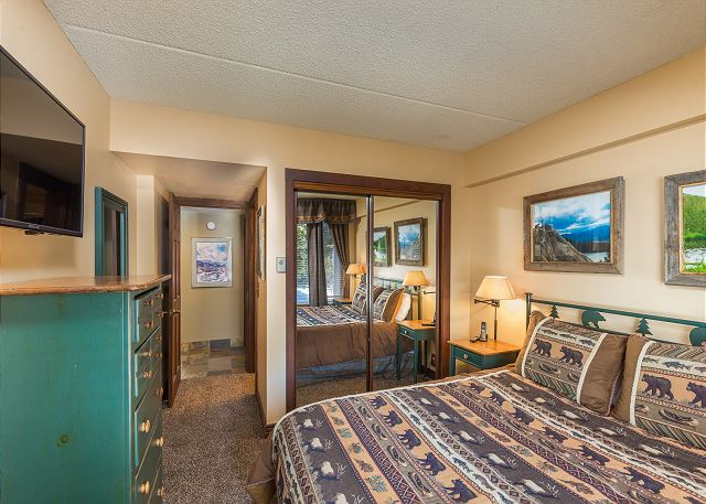 The first guest bedroom features a queen-sized bed, a mounted flat screen TV and its own access to the guest bathroom.
