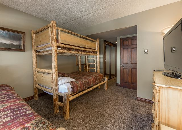 The second guest bedroom has two twin-over-full bunk beds and a flat screen TV.
