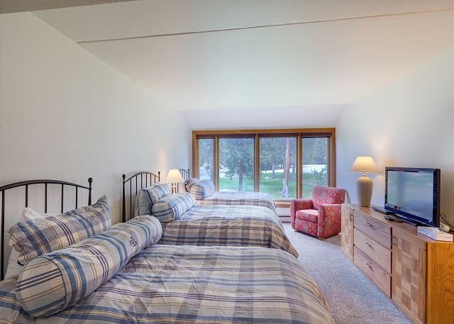 The second guest bedroom features three twin-sized beds and flat screen TV with DVD player.