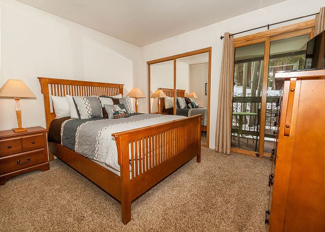 The first guest bedroom features a queen-size bed, a mounted flat screen TV and its own access to the private deck.