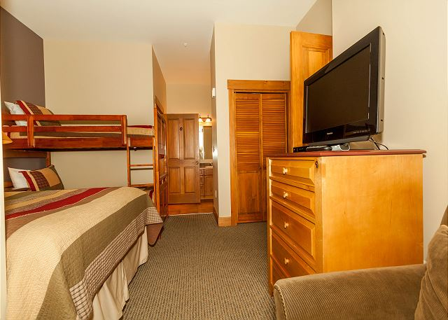 The guest bedroom features a queen-sized bed, a bunk bed and a flat screen TV. It also has an en suite bathroom.