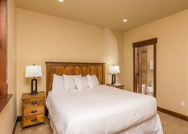 The first guest bedroom is downstairs and features a king-sized bed with Ivory White Bedding and its own access to the guest bathroom.