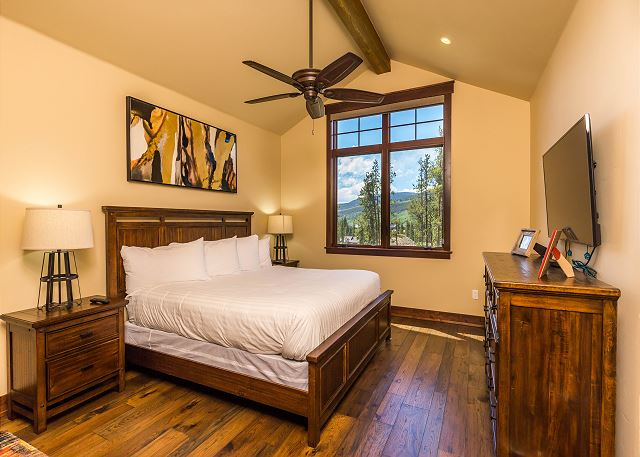 The master bedroom features a king-sized bed with Ivory White Bedding and a mounted flat screen TV.
