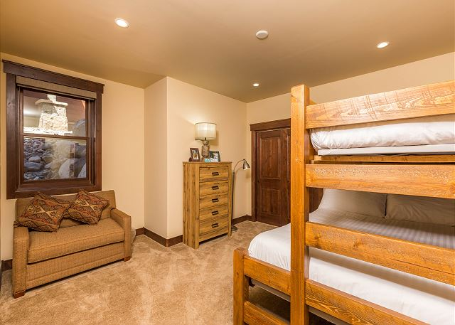 The second guest bedroom is downstairs and sleeps three with a twin-over-queen bunk bed with Ivory White Bedding.