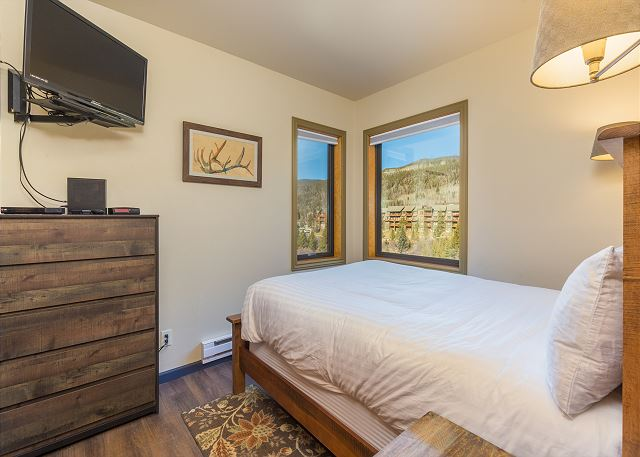 The first bedroom features a queen-sized bed with Ivory White Bedding, a flat screen TV and mountain views.