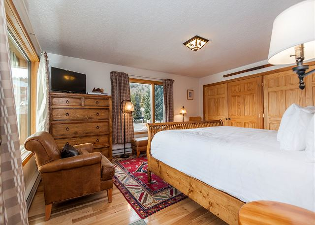 The master bedroom features a king-sized bed, a flat screen TV and beautiful lake views.