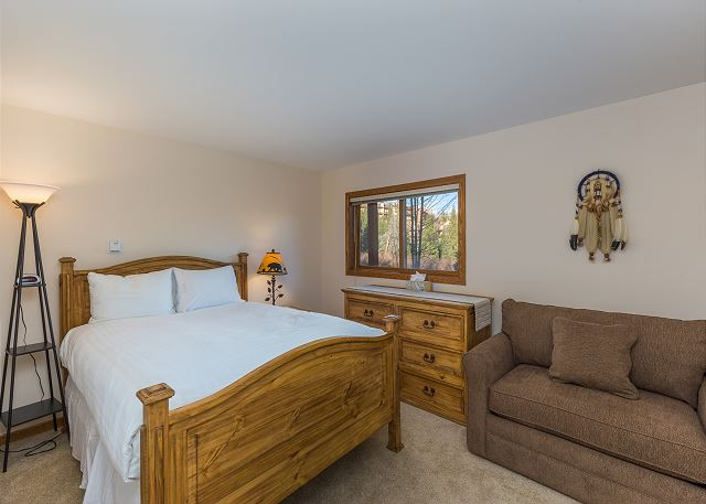 The bedroom features a queen-sized bed with Ivory White Bedding and a twin-sized sleeper chair.