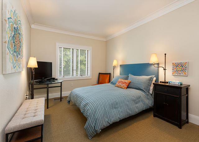 The second guest bedroom features a queen-sized bed, a flat screen TV and its own private bathroom.