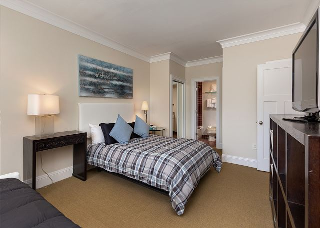 The first guest bedroom features a flat screen TV, a queen-sized bed and a twin-sized daybed. It also has its own private bathroom.