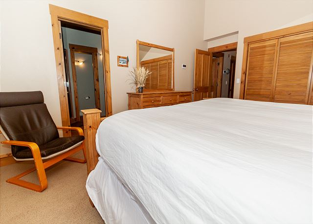 The spacious master bedroom features a king-sized bed and a comfortable chair.
