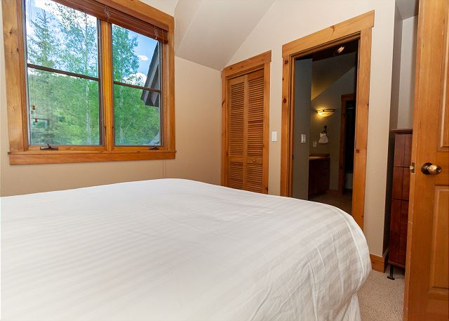 The first guest bedroom features a queen-sized bed and shares a bathroom with the second guest bedroom.
