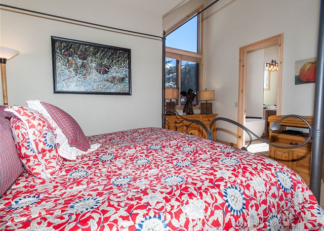 The master bedroom features a king-sized bed, vaulted ceilings and beautiful views.