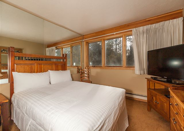 The first guest bedroom features a queen-sized bed with Ivory White Bedding, a flat screen TV and its own private vanity.