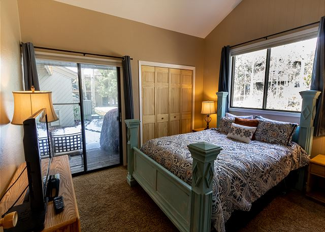 The first guest bedroom features a queen-sized bed, a flat screen TV and access to the private patio.