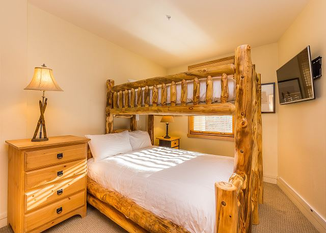 The guest bedroom features a twin-over-queen bunk bed with Ivory White Bedding and a mounted flat screen TV.