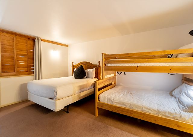The upstairs bedroom features a queen-sized bed, a twin-over-full bunk bed and a flat screen TV.