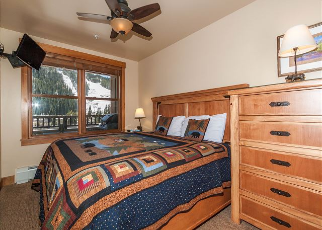 The first master bedroom features a king-sized bed, a mounted flat screen TV and stunning slope views.