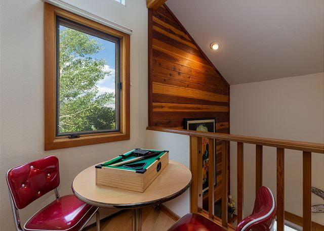 The upstairs loft is the second guest bedroom and it features a king-sized bed and a two-person game table.
