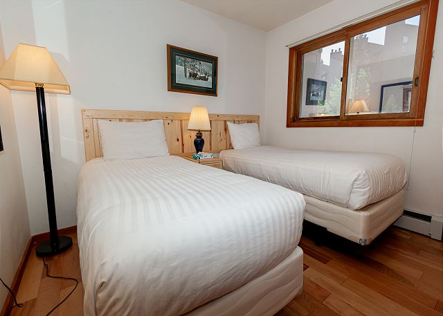 The first guest bedroom is on the main level and has two twin-sized beds and a flat screen TV.
