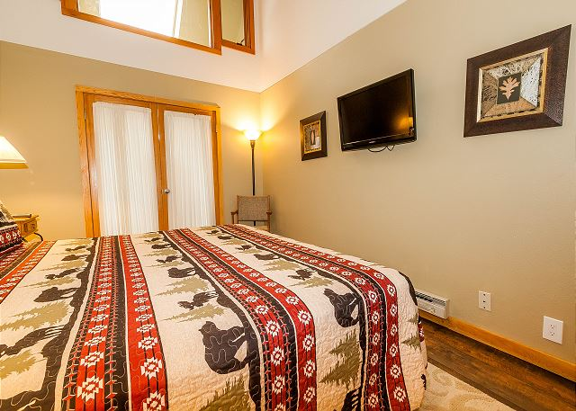 The master suite features a king-sized bed and a mounted flat screen TV. It also has access to the first guest bedroom.