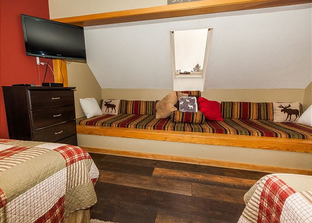 The upstairs loft serves as the second guest bedroom and it has two queen-sized beds, two twin-sized cushioned benches and a mounted flat screen TV.
