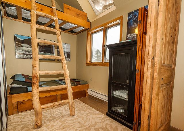 This small area sectioned off area from the sunroom has a built-in twin-sized bunk bed and a skylight.