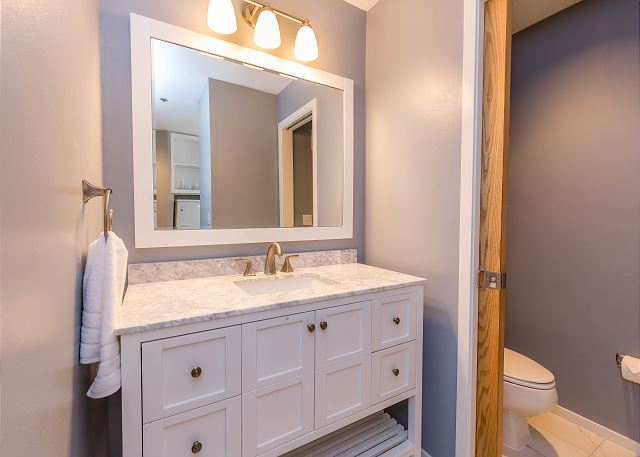 There is a half bathroom near the living area with a single sink vanity and a door separates the toilet area for added privacy.