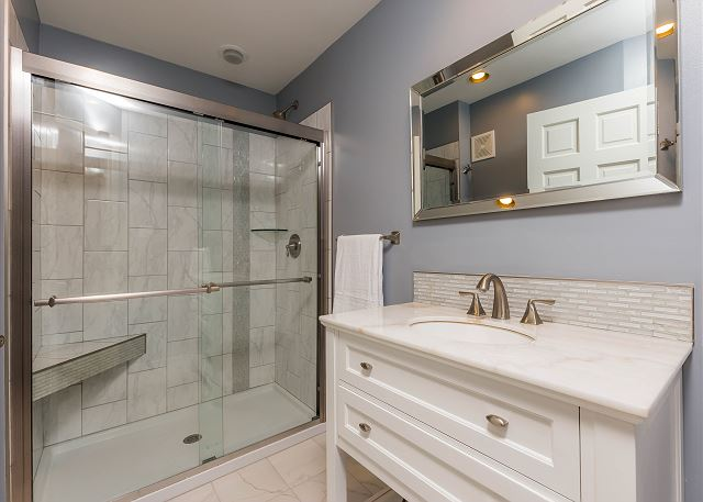 There is a half bathroom across from the bedroom with a walk-in shower and a single sink vanity.