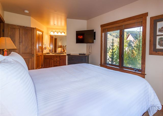 The master bedroom features a king-sized bed, flat screen TV and beautiful slope views.