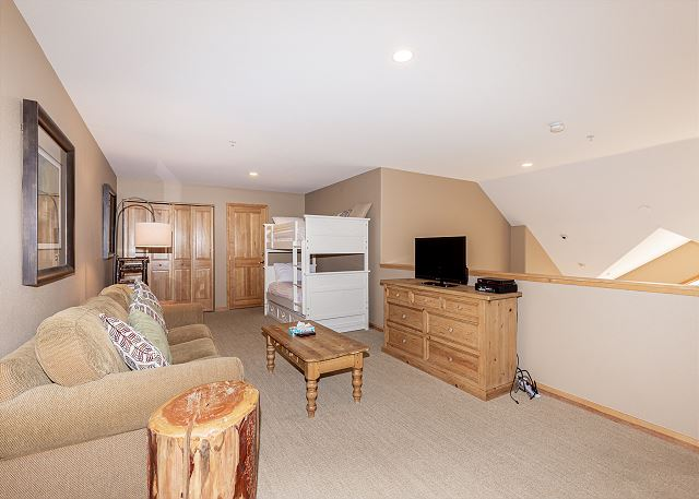 The loft features a flat screen TV, queen-sized sleeper sofa and a twin-sized bunk bed.