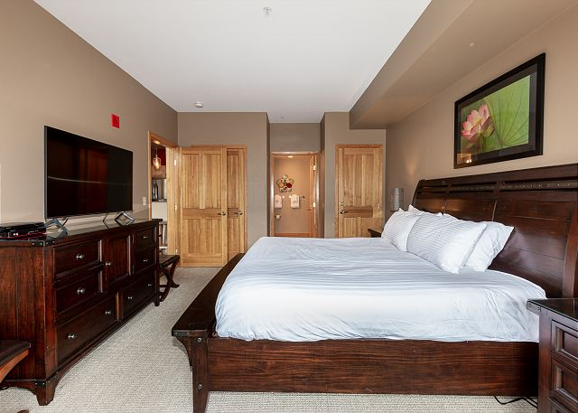 The first master bedroom features a king-sized bed, a mounted flat screen TV and its own entrance to the private balcony.