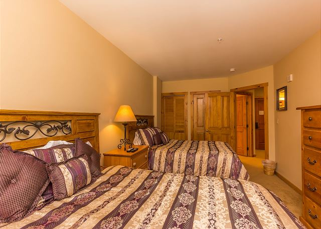 The guest bedroom features two queen-sized beds and a mounted flat screen TV.