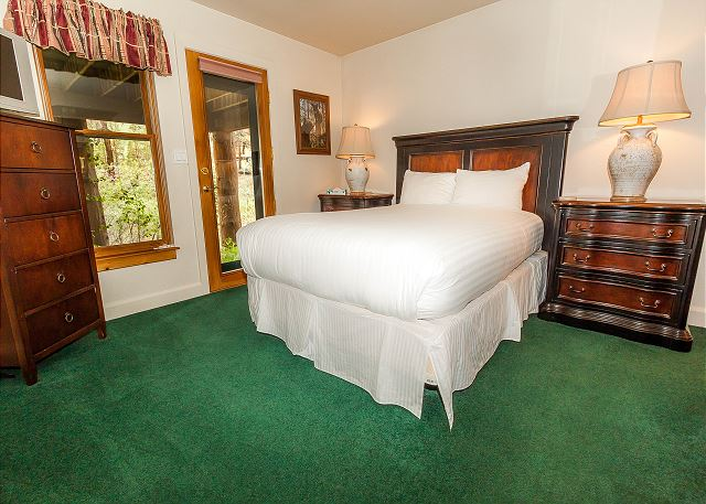 The first guest bedroom is downstairs and features a queen-sized bed with Ivory White Bedding, a flat screen TV and outdoor access.
