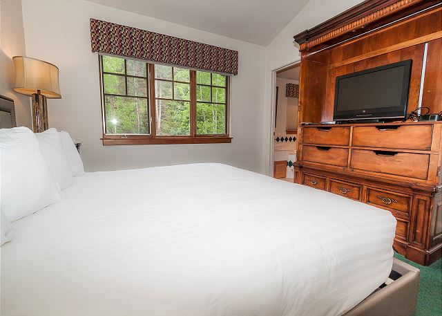 The master bedroom is upstairs and features a king-sized bed with Ivory White Bedding and a flat screen TV.