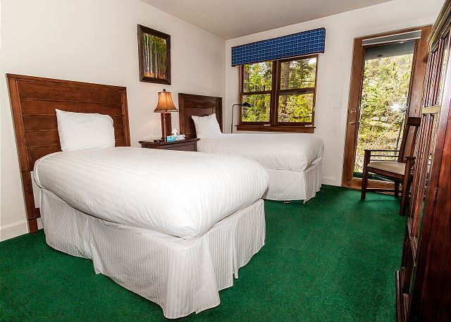 The second guest bedroom is downstairs and features two twin-sized beds with Ivory White Bedding, a flat screen TV and outdoor access.
