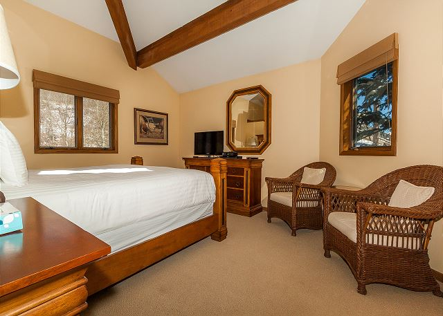 The first master bedroom features a king-sized bed with Ivory White Bedding, a seating area and a flat screen TV.