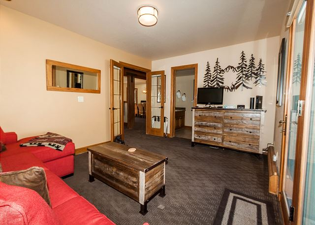 The den is also the first guest bedroom on the main level and has a queen-sized sleeper sofa, a flat screen TV and access to the private deck.