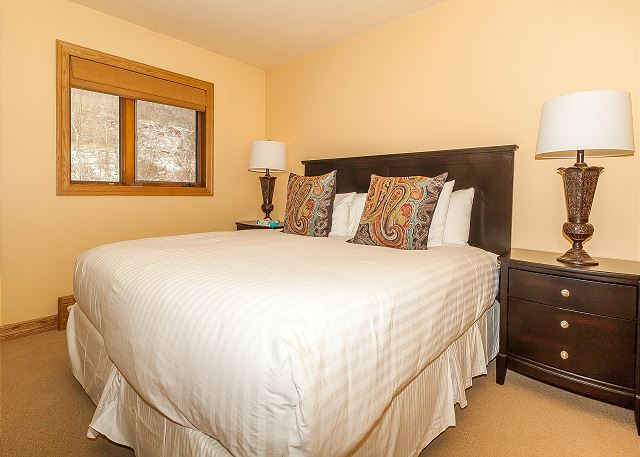 The second master bedroom features a king-sized bed with Ivory White Bedding, a flat screen TV and an en suite bathroom.