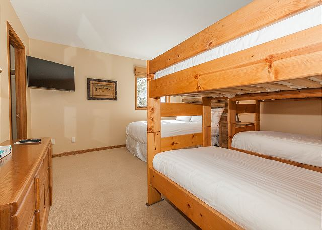 The second guest bedroom sleeps six with two twin-sized bunk beds and a queen-sized bed, all with Ivory White Bedding. There is also a flat screen TV and an en suite bathroom.