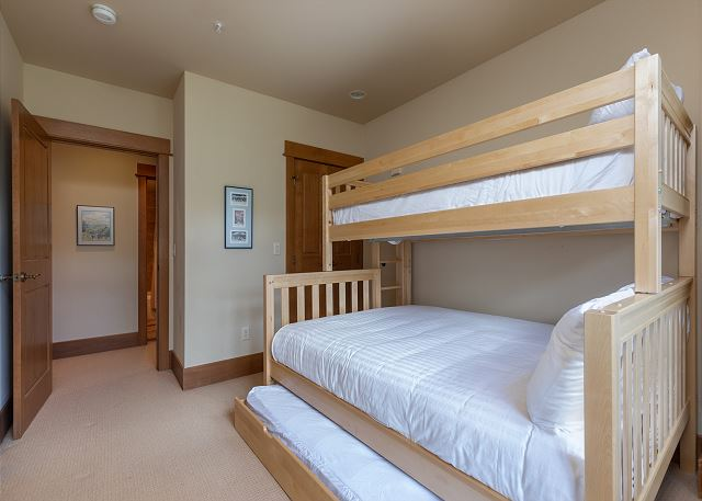 The guest bedroom features a twin-over-queen bunk bed with Ivory White Bedding and a twin trundle and a flat screen TV.