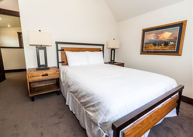 The second master bedroom is upstairs and features a queen-sized bed with Ivory White Bedding and a mounted flat screen TV.