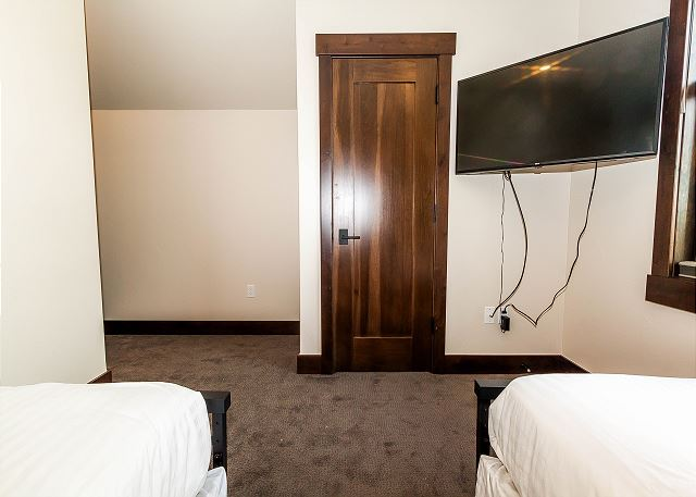 The guest bedroom features two twin-sized beds with Ivory White Bedding, a mounted flat screen TV and its own private bathroom.