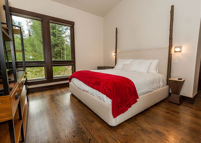 The first master bedroom is on the main level and features a king-sized bed with Ivory White Bedding, a flat screen TV and a private patio.