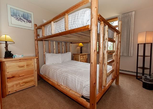 The guest bedroom features a queen-over-queen bunk bed with ivory white bedding.