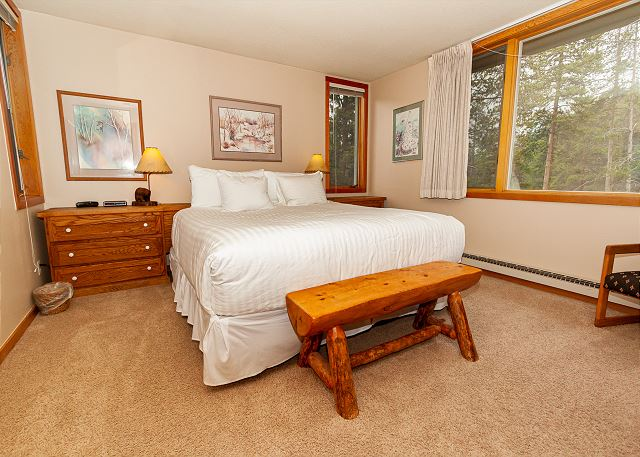 The master bedroom features a king-sized, ivory white bedding , a mounted flat screen TV and scenic views