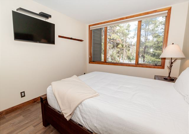 The guest bedroom features a queen-sized bed and a mounted flat-screen TV.