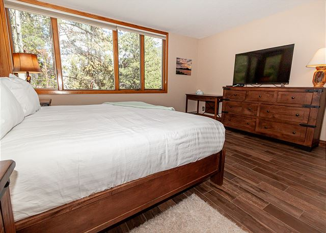 The master bedroom features a king sized bed and flat-screen TV.