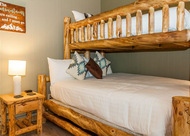 The guest bedroom features a twin-over-queen bunk bed, a flat screen TV and access to the main deck.