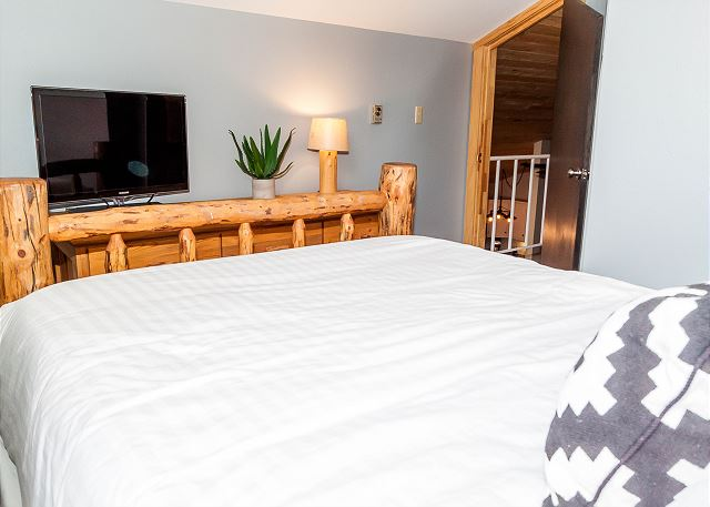 The master bedroom is in the upstairs loft and features a queen-sized bed, a flat screen TV and vaulted ceilings.